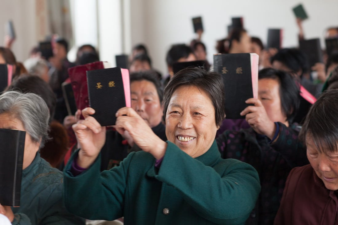 A congregation in China display their Bibles